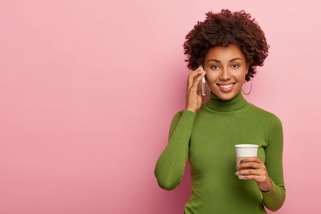 アフロの髪型のかなり魅力的な女性は、携帯電話で友達に電話し、テイクアウトコーヒーを飲み、楽しい話をし、幸せに笑い、良いニュースについて話し合い、カジュアルな緑のジャンパーを着て、屋内でポーズをとる 無料写真