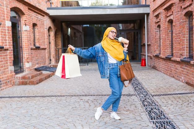 ショッピングモールの後に買い物袋を持つかなりアラブの女性 Premium写真
