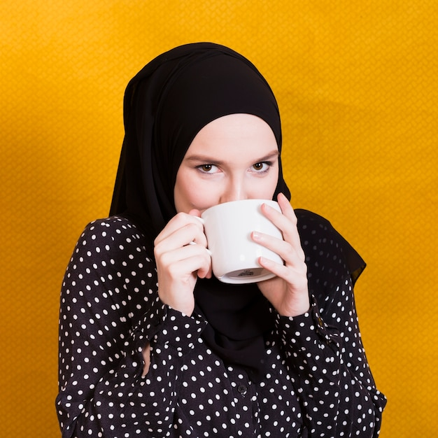 Pretty arabian woman drinking beverage in cup against surface Free Photo