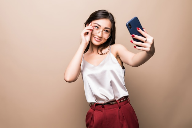Pretty asian girl take selfie with her smart phone isolated on beige wall. Free Photo