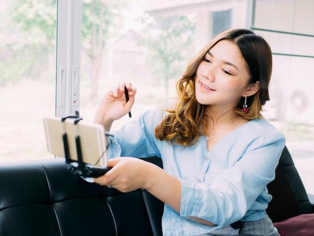 かなりアジアの女性は製品をレビューするためのオンラインブロガーです Premium写真
