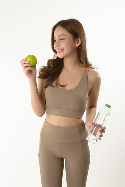 Pretty asian woman with apple and water on white Premium Photo