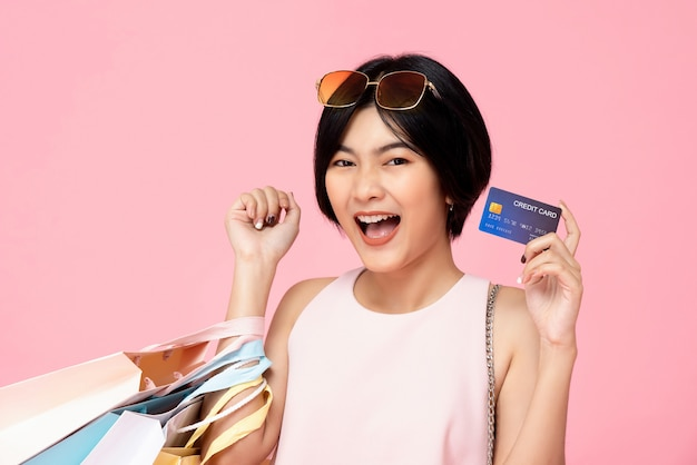 Pretty asian woman with shopping bags showing credit card Premium Photo