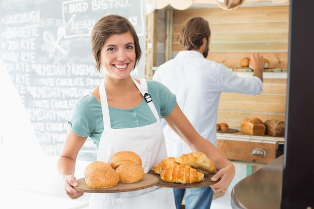 Pretty barista holding trays of baked goods Premium Photo