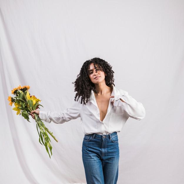 Pretty black woman holding flowers bouquet Free Photo