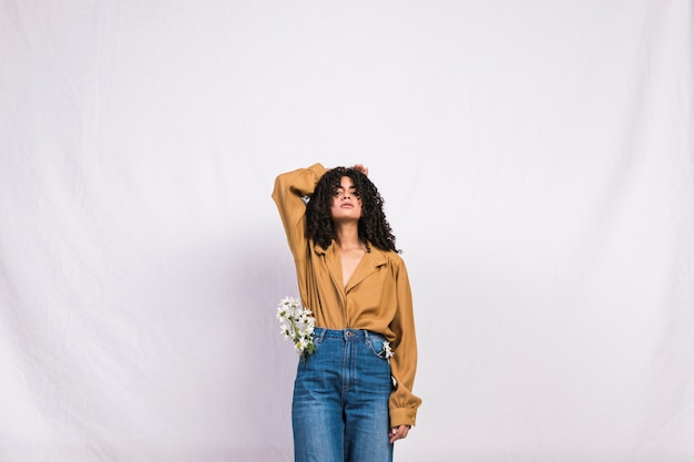 Pretty black woman with daisy flowers in jeans pocket Free Photo