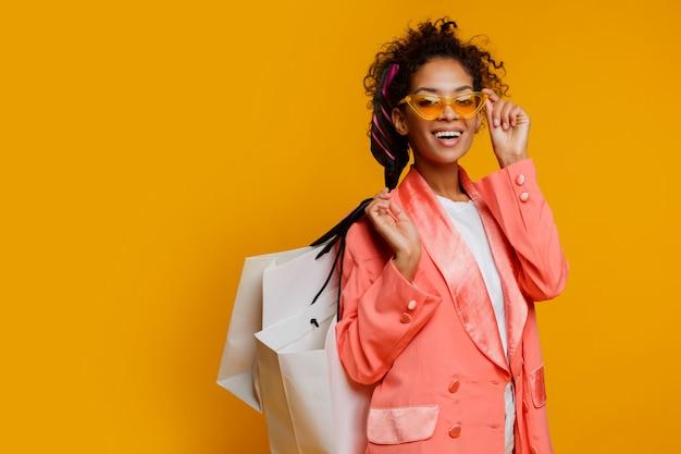 Милая чернокожая женщина при белая хозяйственная сумка стоя над желтой предпосылкой. модный весенний модный образ. Бесплатные Фотографии