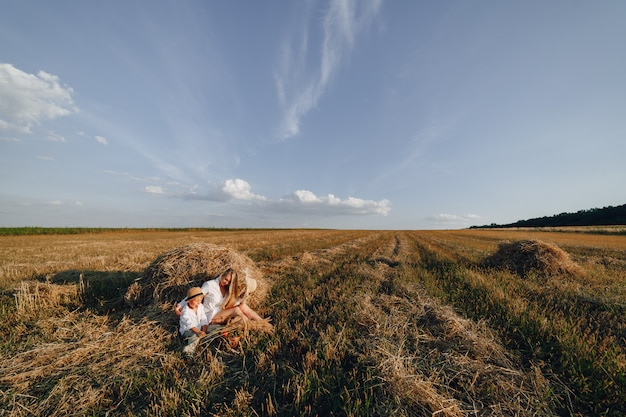 Pretty blond long-haired woman with little blond son at sunset relaxing in the field and savoring fruit from a straw basket. summer, farming, nature and fresh air in the countryside. Free Photo