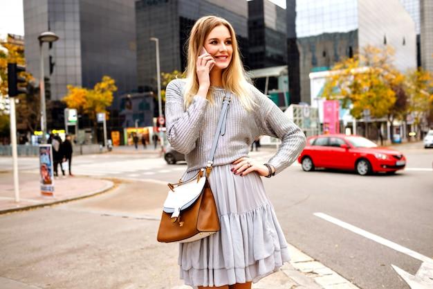都市の建物、灰色のセーター、フェミニンなスカートの近くの通りに彼女の電話で話すかなりブロンドの女性 無料写真