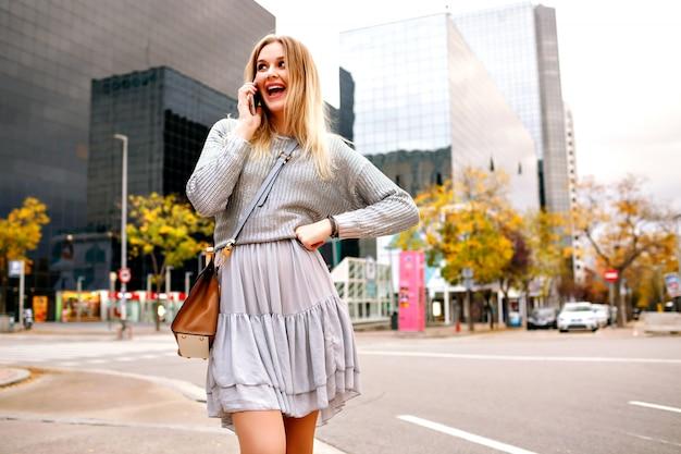 Довольно белокурая женщина разговаривает по телефону на улице возле городских зданий, серый свитер и женственная юбка Бесплатные Фотографии
