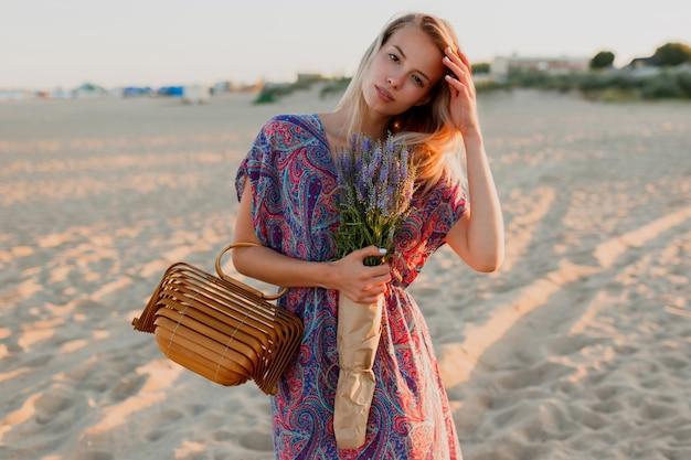 Довольно блондинка женщина с букетом лаванды, ходить на пляж. цвета заката. Бесплатные Фотографии