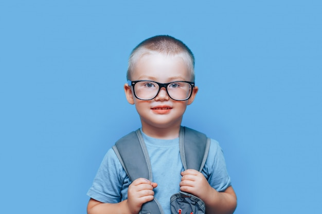 Pretty blonde boy on blue background with backpack Premium Photo