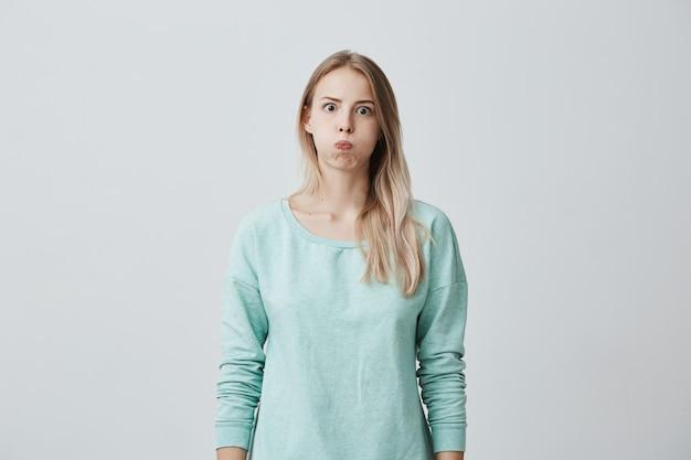 唇が丸みを帯びたかなりブロンドのヨーロッパの女性モデル、驚きに見え、困惑した表情で彼女の感情を表現しています 無料写真