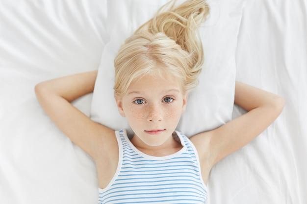 彼女の穏やかな輝く目で直接見て、かなり金髪のそばかすのある青い目の女の子が白い寝具のベッドで横になっています。 無料写真