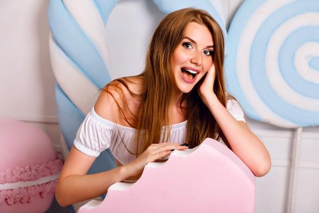 거대한 단맛, 막대 사탕, 아이스크림, 마카롱, 귀여운 유행 여성 의상, 긴 머리카락, 파스텔 색상, 긍정적 인 분위기 근처에서 재미있는 예쁜 금발 소녀. 무료 사진
