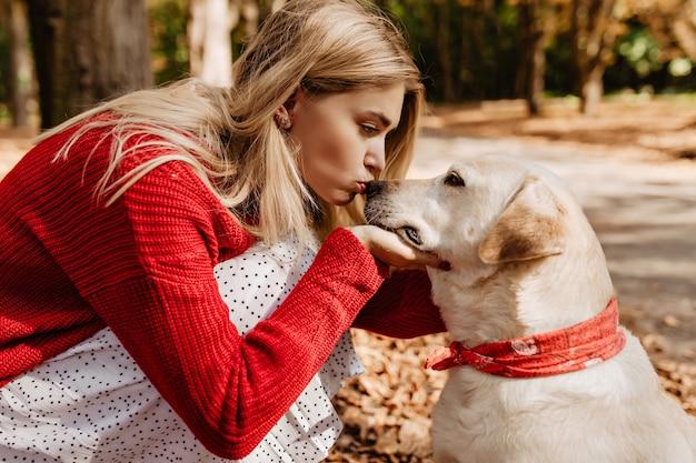 그녀의 아름 다운 래브라도 키스 꽤 금발 소녀입니다. 가 공원에 그녀의 강아지와 함께 붉은 색을 입고 젊은 여자. 무료 사진