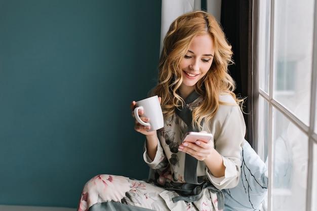 컵 커피, 차, 스마트 폰 손에 창틀에 앉아 예쁜 금발 소녀. 그녀는 긴 금발의 물결 모양의 머리카락, 미소를 지으며 휴대 전화를보고 있습니다. 아름다운 실크 파자마를 입고 있습니다. 무료 사진