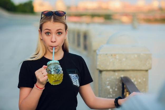 Довольно блондинка с бокалом освежающего лимонада Premium Фотографии