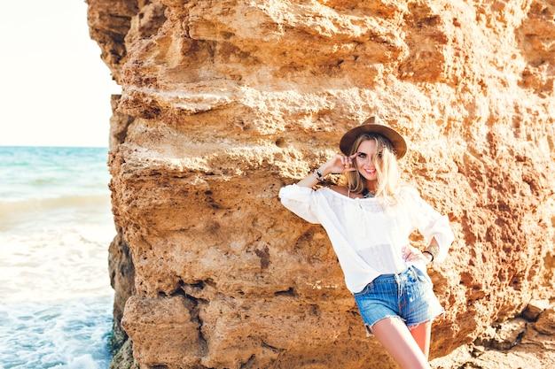長い髪のかなりブロンドの女の子は、石の背景にビーチでカメラにポーズをとっています。彼女は微笑んでいる。 無料写真