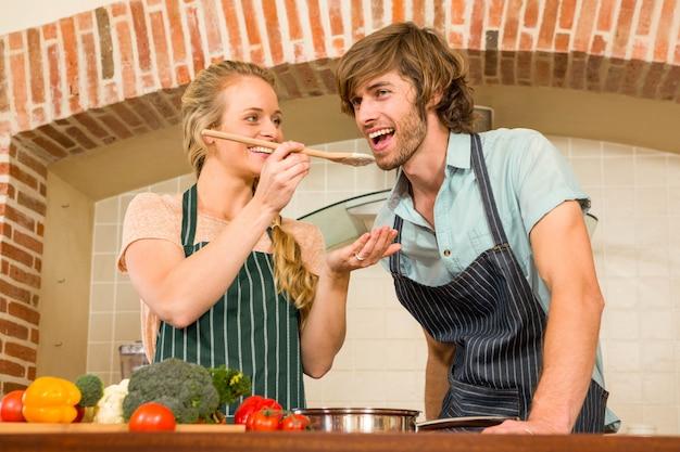 Pretty blonde making her boyfriend taste the preparation in the kitchen Premium Photo