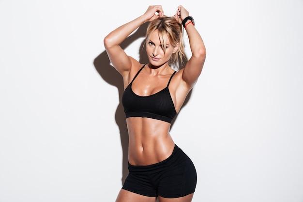 예쁜 금발 Sportswoman 서있는 동안 포즈 무료 사진