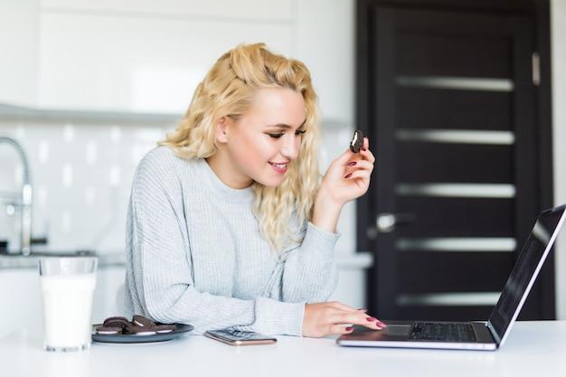 台所のテーブルに座っている間にラップトップコンピューターを使用してクッキーを食べて、ガラスから牛乳を飲むかなりブロンドの女性 無料写真