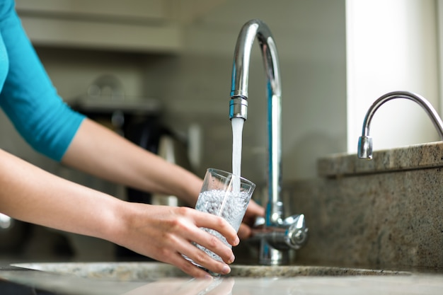 Pretty blonde woman filling a glass of water Premium Photo