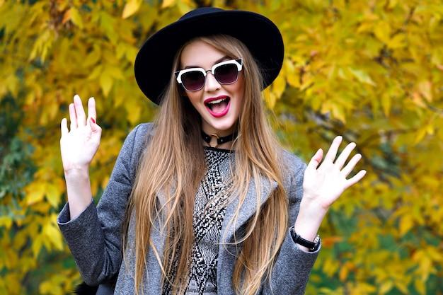 Donna abbastanza bionda che si diverte al parco cittadino in una fresca giornata autunnale, vestito alla moda elegante, sciarpa, occhiali da sole cappello, girocollo, elegante stile di strada Foto Gratuite