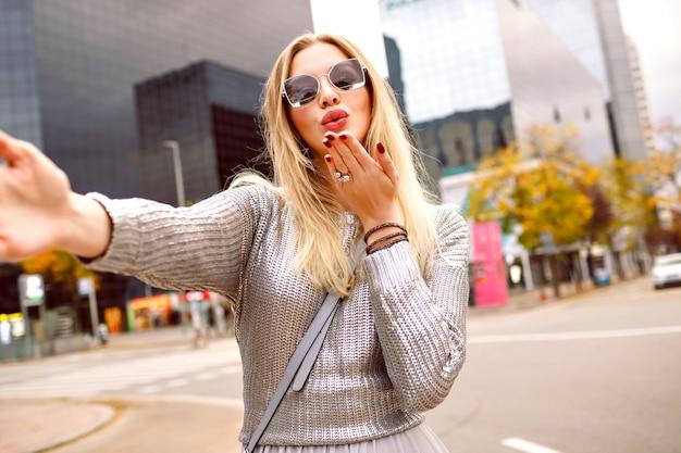 近代的な建物エリアの近くの通りでselfieを作るかなりブロンドの女性、灰色のセーターと華やかなアクセサリーを身に着けて、空気のキス、ロマンチックな気分、幸せな観光女性、春秋の時間を送信します。 無料写真