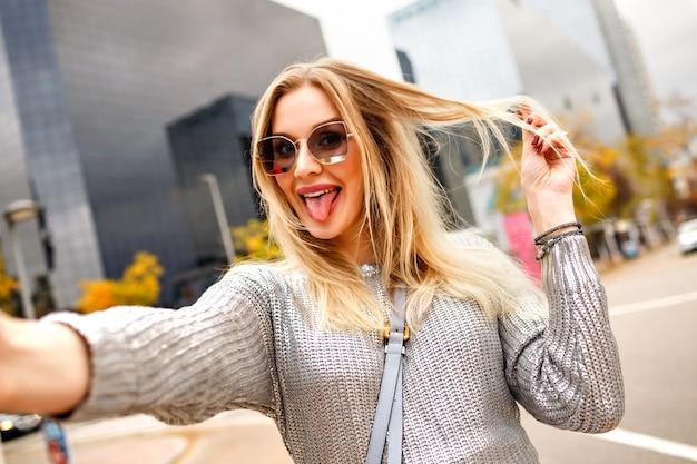 近代的な建物のエリアの近くの通りでselfieを作るかなりブロンドの女性、灰色のセーターと魅力的なアクセサリーを身に着けて、長い舌、幸せな観光客、前向きな気分を示します。 無料写真