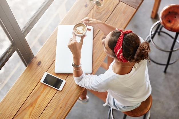 Довольно блондинка сидит в кафе вид сверху Бесплатные Фотографии