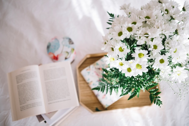 Pretty bouquet on tray near opened book Free Photo