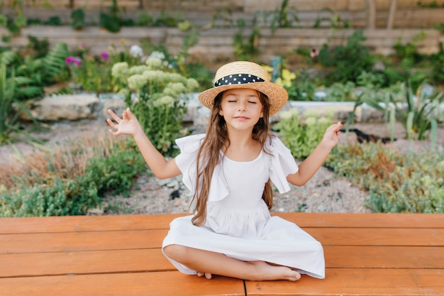 Pretty brunette female kid in straw hat sitting near flowerbed in lotus pose with eyes closed. little girl in white dress doing yoga in garden Free Photo