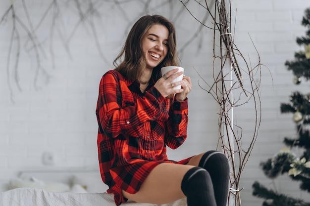赤いシャツとコーヒーのカップと暖かい靴下を身に着けているベッドでかなりブルネットの女の子 Premium写真