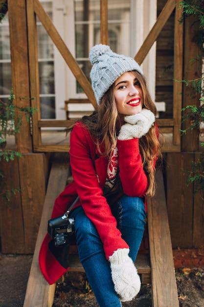 赤いコート、ニット帽子、屋外の木製の階段に座っている白い手袋でかなりブルネットの少女。彼女は長い髪をして、笑っています。 無料写真