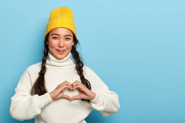 Bella ragazza mora fa il segno della mano del cuore, sorride piacevolmente, indossa un cappello giallo e un maglione bianco, esprime amore e affetto, ha un'espressione soddisfatta, modelli su sfondo blu, spazio di copia Foto Gratuite