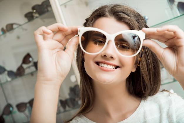 かなりブルネットの少女の笑顔、サングラスの光学ショップで試着 無料写真