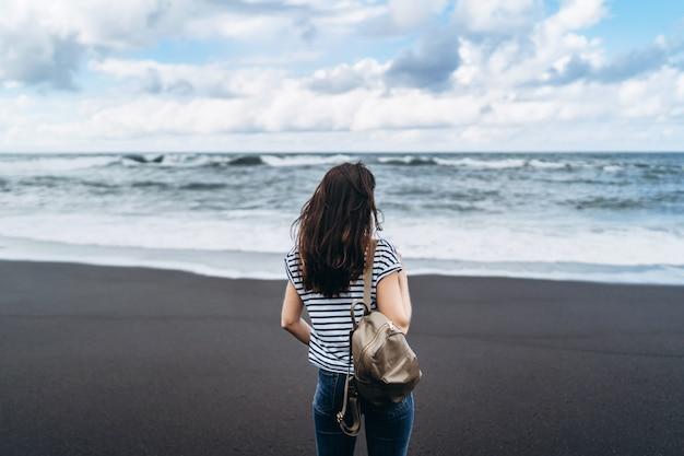 Pretty brunette girl walking on the black sand beach. Premium Photo