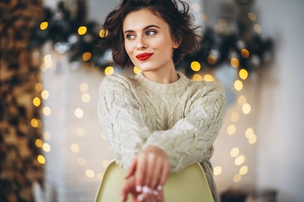 自宅で暖かいセーターを着たかなりブルネット Premium写真
