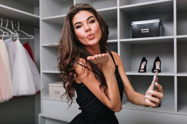 Pretty brunette with long brown curly hair, young girl sending kiss, holding smartphone in hand. big nice dressing room. she sending kiss. wearing stylish dress. Free Photo