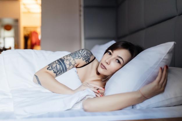 かなりブルネットの女性はファッションモダンなアパートで朝の枕のベッドに産む 無料写真