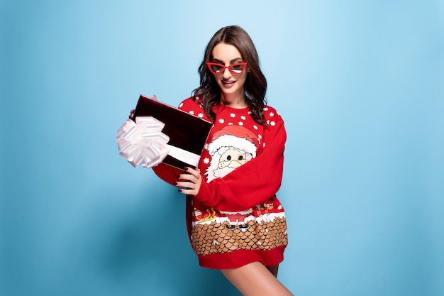 Pretty brunette woman in sunglasses and red oversize pullover with santa design with gift box Premium Photo