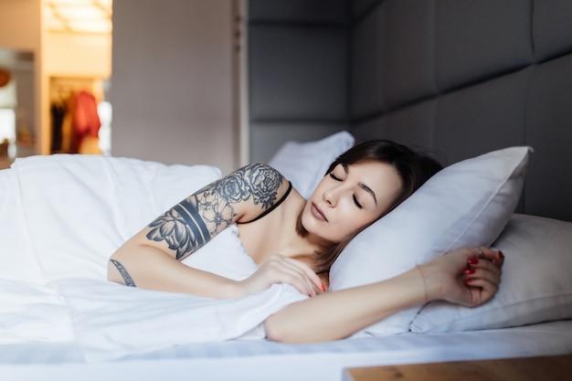 入れ墨を持つかなりブルネットの女性は、ファッションのモダンなアパートで朝の枕のベッドで産む 無料写真