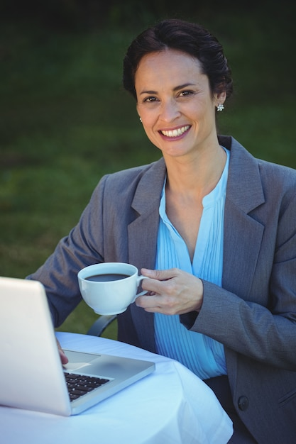 Pretty businesswoman having coffee and using laptop Premium Photo