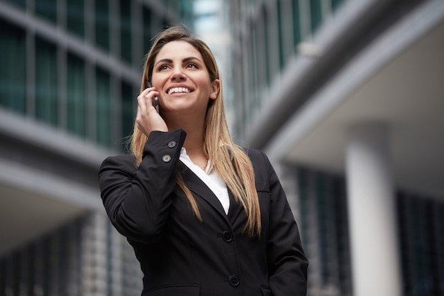 Pretty businesswoman talking to mobile in urban environment Premium Photo