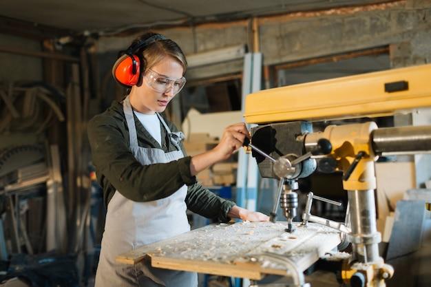 Pretty carpenter using drill press Free Photo