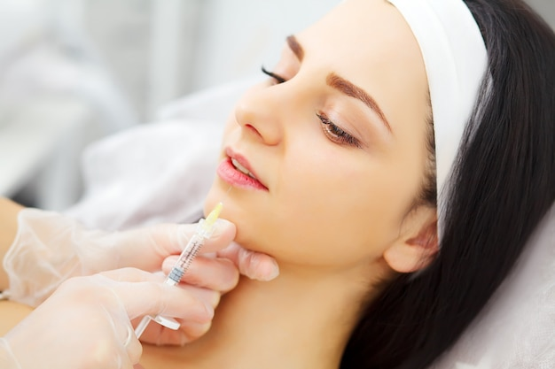 Pretty caucasian female having of hyaluronic acid injection in face zone Premium Photo