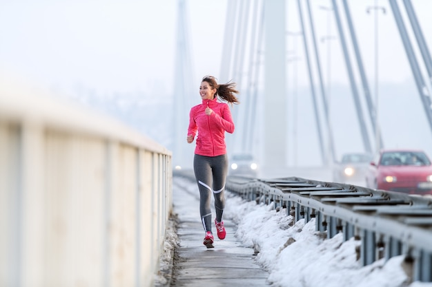 Pretty caucasian woman with ponytail dressed in sportswear running on the bridge at winter. healthy lifestyle concept. Premium Photo