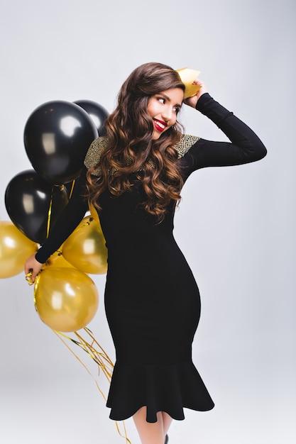 Довольно очаровательная девушка с длинными вьющимися волосами брюнетка празднует день рождения на белом Бесплатные Фотографии