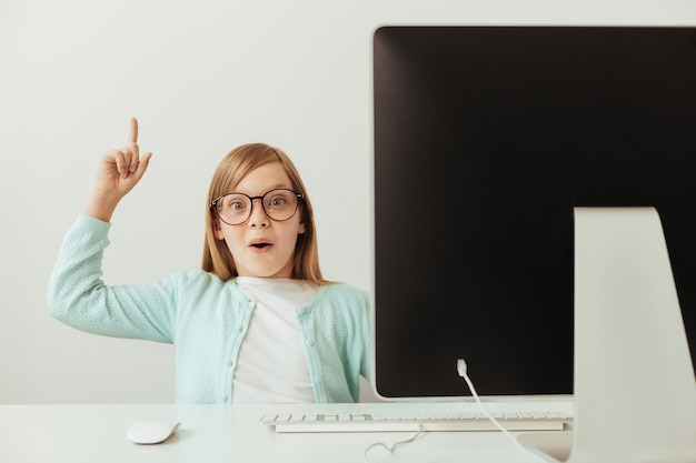 Pretty charming intelligent girl using her computer for learning new things and telling about them Premium Photo